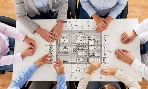 business, people, architecture and team work concept - close up of architects team hands and blueprint on office table